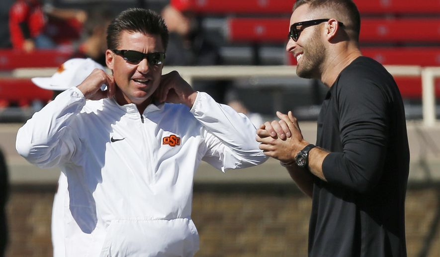 FILE - In this Oct. 31, 2015, file photo, Oklahoma State head coach Mike Gundy, left, talks with Texas Tech head coach Kliff Kingsbury, right, before an NCAA college football game in Lubbock, Texas. The two teams meet on Saturday. (AP Photo/Sue Ogrocki, File)