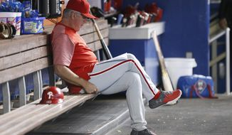 FILE - In this Sept. 2, 2017, file photo, Philadelphia Phillies manager Pete Mackanin sits in the dugout before the start of a baseball game against the Miami Marlins in Miami. The Phillies announced Friday, Sept. 29, 2017, that Mackanin will be replaced for next season. (AP Photo/Wilfredo Lee, File)
