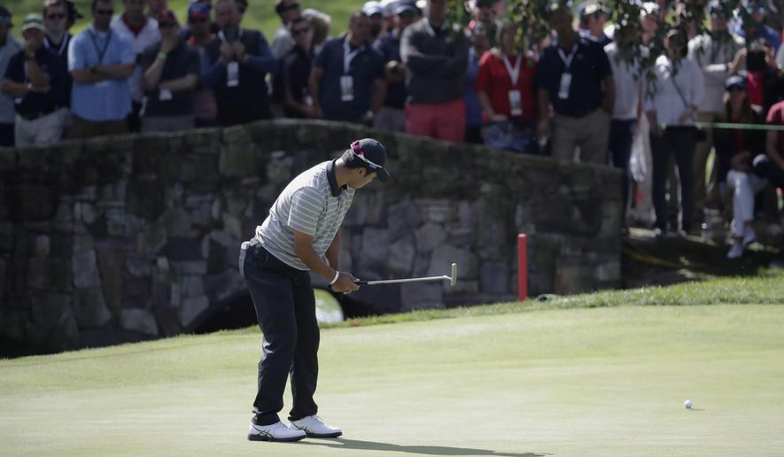 Hideki Matsuyama putts on the first green during the four-ball golf matches on the second day of the Presidents Cup at Liberty National Golf Club in Jersey City, N.J., Friday, Sept. 29, 2017. (AP Photo/Julio Cortez)
