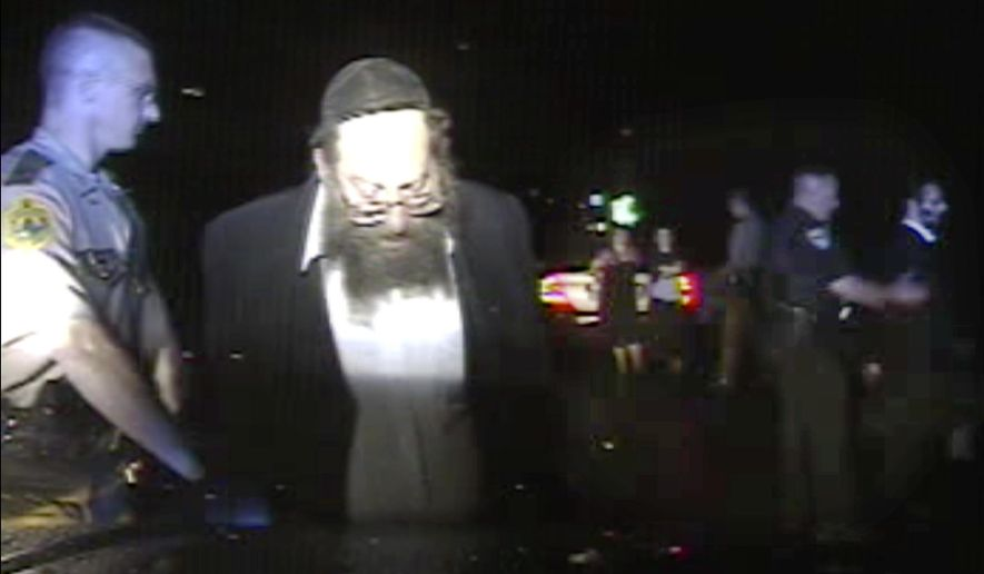 In this Aug. 8, 2017, still frame from dashboard camera video released by the Vermont State Police, Trooper Justin Thompson, left, detains driver Rabbi Berl Fink, while a second officer, right, detains passenger Rabbi Eli Fink, both of of Brooklyn, N.Y., during a traffic stop in Thetford, Vt. An internal investigation of the nighttime traffic stop of the rabbi, who was ordered at gunpoint to the ground and his family handcuffed after he failed to stop, has cleared the trooper of wrongdoing. State police officials said Friday, Sept. 29, 2017, that Thompson clocked the vehicle at 83 miles per hour on Interstate 91, and he tried to stop the vehicle with lights and siren but it failed to stop for 4.5 miles. (Vermont State Police via AP)