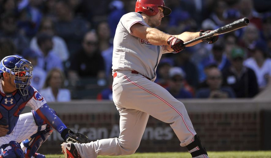Cincinnati Reds' Scott Schebler, right, watches his RBI-single during the fifth inning of a baseball game against the Chicago Cubs, Friday, Sept. 29, 2017, in Chicago. (AP Photo/Paul Beaty)