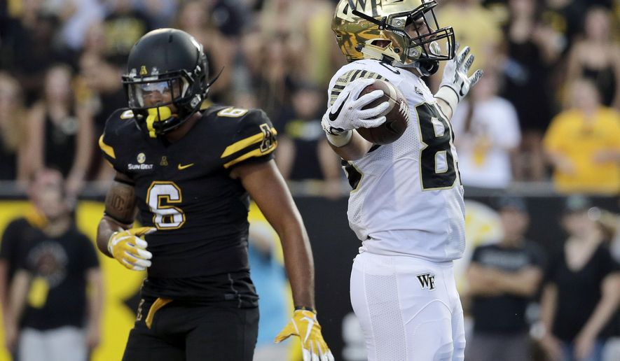 Wake Forest tight end Cam Serigne (85) celebrates his touchdown catch as Appalachian State defensive back Desmond Franklin (6) walks past during the second half of an NCAA college football game in Boone, N.C., Saturday, Sept. 23, 2017. (AP Photo/Chuck Burton)