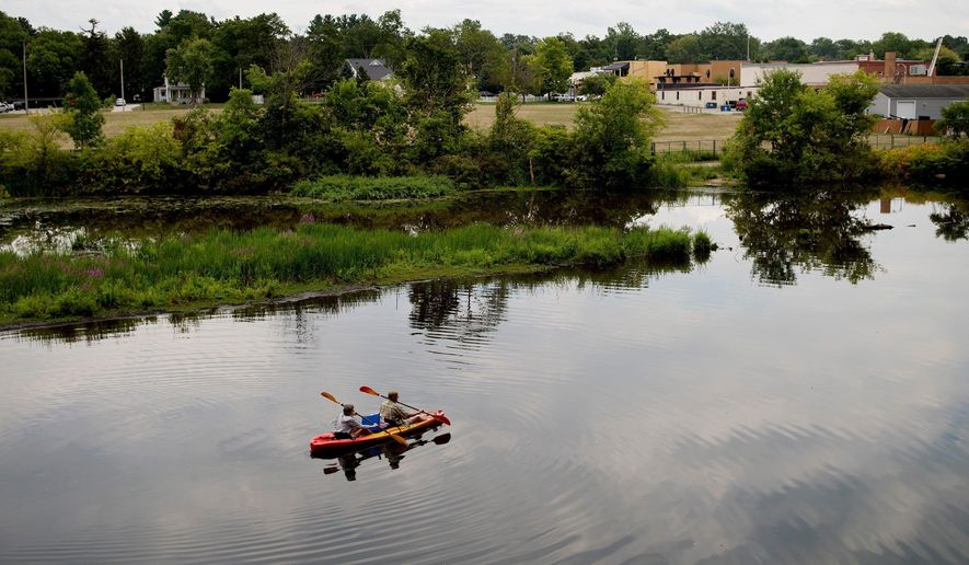 In this Monday, Aug. 14, 2017 photo, a couple kayak on the Rogue River adjacent to where Wolverine World Wide's tannery once stood, in Rockford, Mich. The Michigan Department of Environmental Quality is investigating the connection between old waste drums in the area and an old Wolverine World Wide tannery waste dump nearby. Some private wells in the area have tested positive for elevated levels of per- and polyfluoroalkyl substances called PFAS, also called perfluorinated chemicals, or PFCs. The DEQ says Wolverine dumped sludge containing the chemicals in unlined trenches back in the 1960s. The well contamination was discovered this year.  (Neil Blake /The Grand Rapids Press via AP)