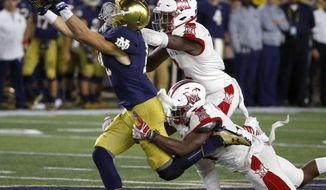Notre Dame wide receiver Chris Finke catches a pass from Ian Book as Miami (Ohio) defensive back Joshua Allen, top, and Deondre Daniels defend during the second half of an NCAA college football game Saturday, Sept. 30, 2017, in South Bend, Ind. Notre Dame won 52-17. (AP Photo/Charles Rex Arbogast)