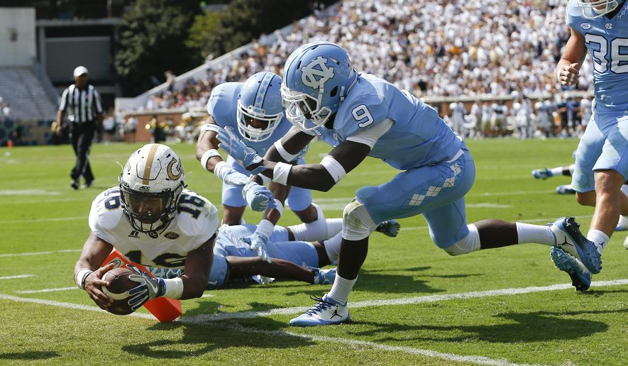 Georgia Tech quarterback TaQuon Marshall (16) dives into the end zone for a touchdown against North Carolina's Dominique Ross (3) and K.J. Sails (9) in the first half of an NCAA college football game Saturday, Sept. 30, 2017, in Atlanta. (AP Photo/John Bazemore)