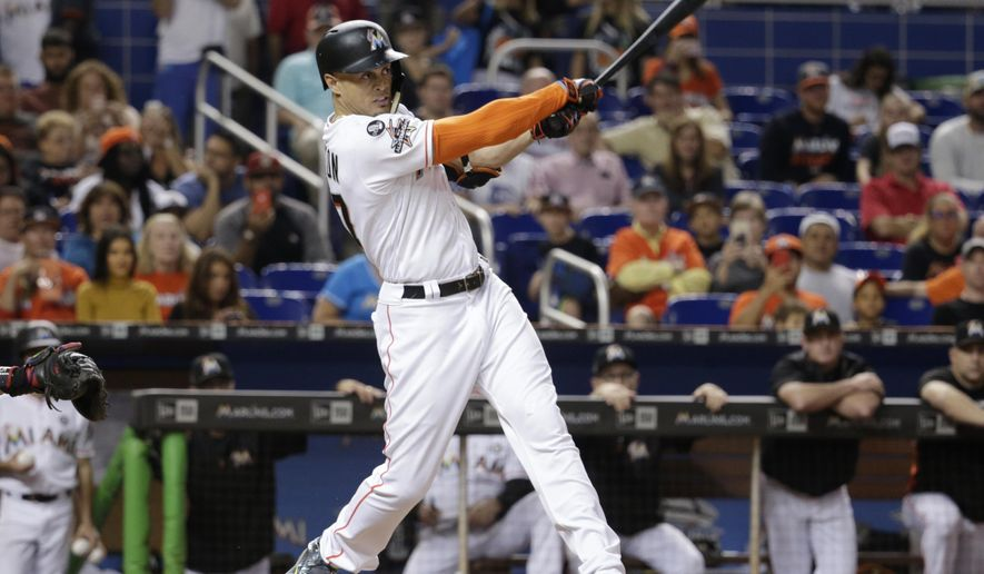 Miami Marlins' Giancarlo Stanton hits a RBI single to score Miguel Rojas during the fifth inning of a baseball game against the Atlanta Braves, Saturday, Sept. 30, 2017, in Miami. (AP Photo/Lynne Sladky)