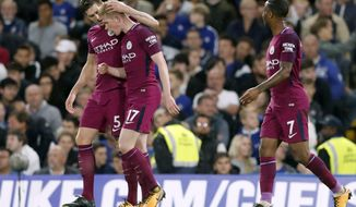 Manchester City's scorer Kevin De Bruyne, 2nd left, and his teammates John Stones, left, and Raheem Sterling, right, celebrate the opening goal during their English Premier League soccer match between Chelsea and Manchester City at Stamford Bridge stadium in London, Saturday, Sept. 30, 2017. (AP Photo/Frank Augstein)
