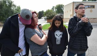 Reese Gunshows, right, his sister Myarae, second from right, his mother Jessie Gunshows and her husband Allen White Bear talk about Reese's recovery on Sept. 24, 2017, on the corner of 12th Street West and Broadwater Avenue where Reece was struck by a car two years ago. ( Larry Mayer/The Billings Gazette via AP)