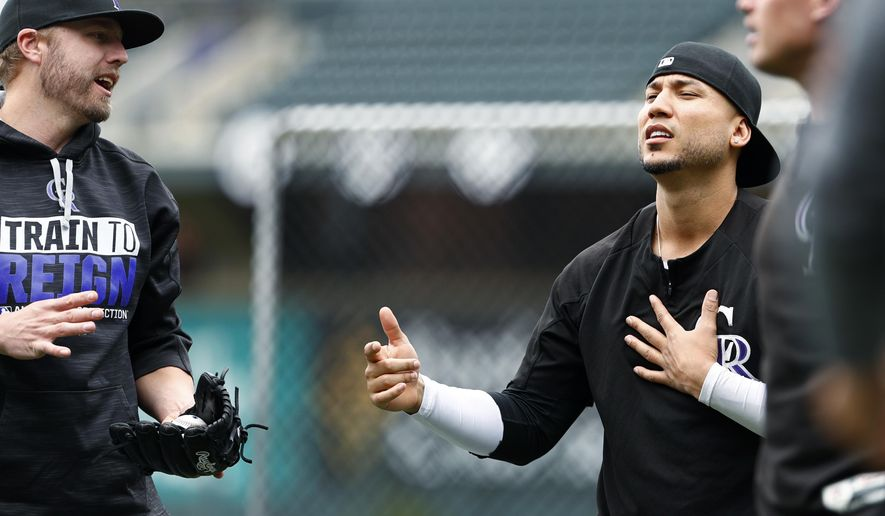 Colorado Rockies right fielder Carlos Gonzalez, right, sings for first baseman Mark Reynolds as they work out around the cage as the team takes batting practice before facing the Los Angeles Dodgers in a baseball game Saturday, Sept. 30, 2017, in Denver. (AP Photo/David Zalubowski)