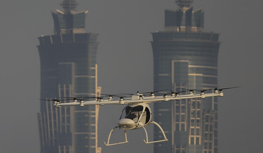 In this Sept. 26, 2017 photo, a Volocopter prototype flies in front of the two hotel towers during a test flight in Dubai, United Arab Emirates. Dubai is hoping to one day have flying, pilotless taxis darting among its skyscrapers. Just this week, the city-state in the United Arab Emirates hosted crews from the German company Volocopter, which had an electric, battery-powered two-seat prototype take off and land. Dubai hopes to have rules in place in the next five years to be ready for having the aircraft regularly flying through its skies. (AP Photo/Kamran Jebreili)