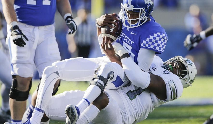 Eastern Michigan defensive lineman Kwanii Figueroa sacks Kentucky quarterback Stephen Johnson for a loss of yards during the first half of an NCAA college football game Saturday, Sept. 30, 2017, in Lexington, Ky. (AP Photo/David Stephenson)