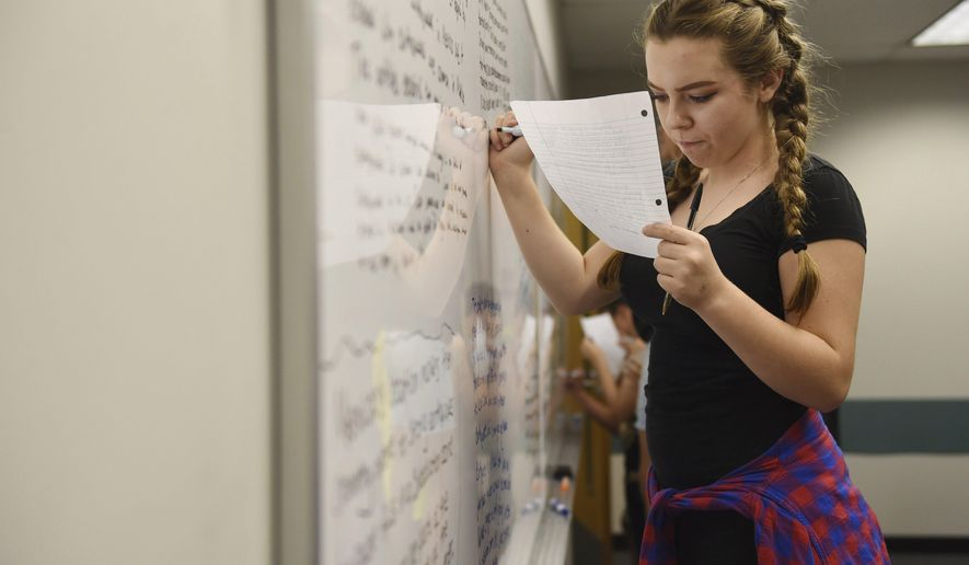 In this Friday, Sept. 22, 2017 photo, a student works at the white board during ninth grade English class in Porter Building at Eastern Michigan University, near Ann Arbor, Mich. The Early College Alliance at EMU has expanded to include a new ninth grade academy this school year. (Melanie Maxwell /The Ann Arbor News via AP)