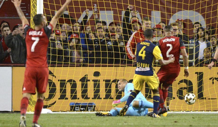 Toronto FC's Justin Morrow, (2) scores against New York Red Bulls' goalkeeper Luis Robles during the first half of an MLS soccer game, Saturday, Sept. 30, 2017, in Toronto. (Jon Blacker/The Canadian Press via AP)