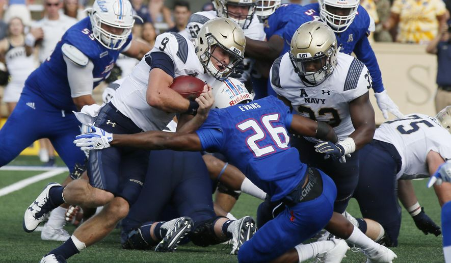 Navy quarterback Zach Abey (9) escapes a tackle by Tulsa cornerback Akayleb Evans (26) on his way to a touchdown in the second quarter of an NCAA college football game in Tulsa, Okla., Saturday, Sept. 30, 2017. (AP Photo/Sue Ogrocki)