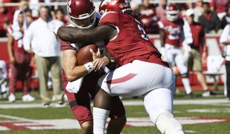 New Mexico State quarterback Tyler Rogers, left, is sacked by Arkansas defender McTelvin Agim during the first half of an NCAA college football game in Fayetteville, Ark., Saturday, Sept. 30 2017. (AP Photo/Michael Woods)