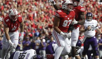 Wisconsin's Isaiahh Loudermilk (97) and Leon Jacobs celebrate after a sack of Northwestern quarterback Clayton Thorson (18) during the first half of an NCAA college football game Saturday, Sept. 30, 2017, in Madison, Wis. (AP Photo/Morry Gash)