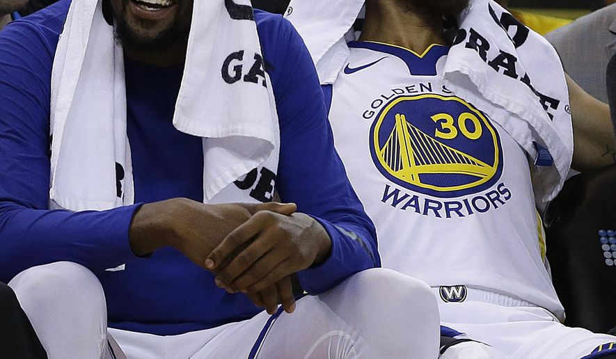 Golden State Warriors' Kevin Durant, left, smiles on the bench beside Stephen Curry (30) during the first half of a preseason NBA basketball game against the Denver Nuggets Saturday, Sept. 30, 2017, in Oakland, Calif. (AP Photo/Ben Margot)