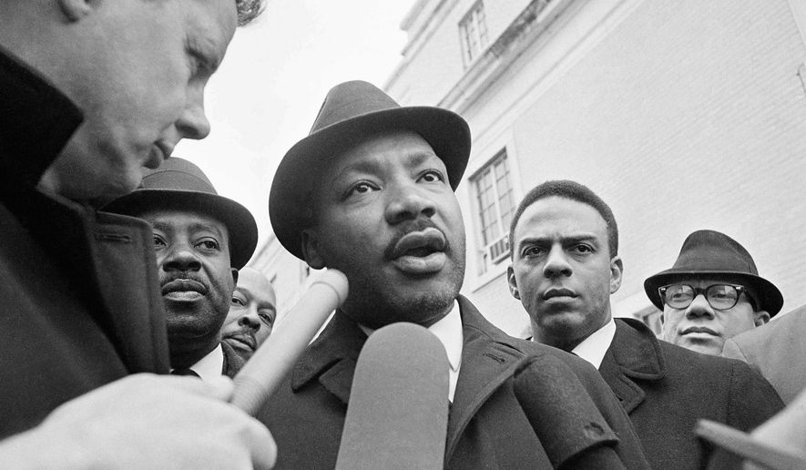 In this Feb. 5, 1965 file photo, Dr. Martin Luther King Jr. is interviewed by newsmen as he left jail in Selma, Ala.