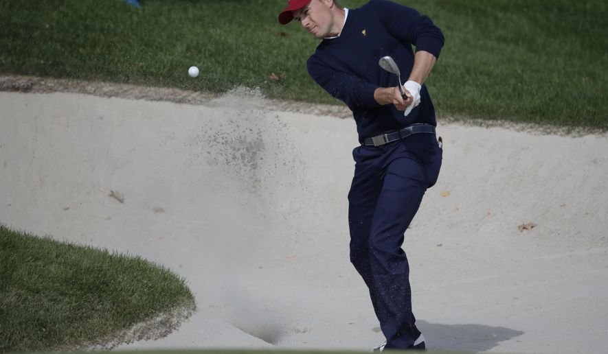 Jordan Spieth hits out of a bunker on the fourth hole during the four-ball golf matches on the third day of the Presidents Cup at Liberty National Golf Club in Jersey City, N.J., Saturday, Sept. 30, 2017. (AP Photo/Julio Cortez)