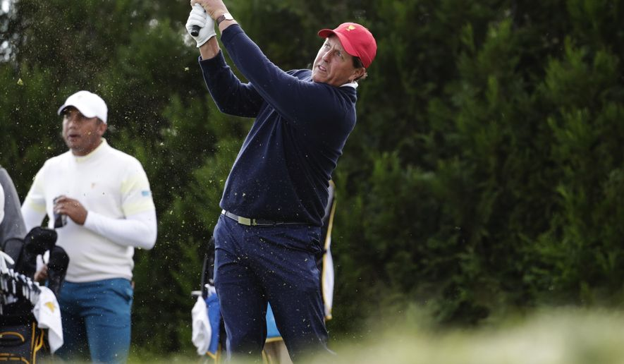 Phil Mickelson tees off on the tenth hole during the third day of the Presidents Cup at Liberty National Golf Club in Jersey City, N.J., Saturday, Sept. 30, 2017. (AP Photo/Julio Cortez)