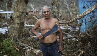 In this Sept. 29, 2017 photo, U.S. Army veteran Luis Cabrera Sanchez holds his machete as he pauses for a portrait while clearing debris from his damaged home, with family and neighbors, in the aftermath of Hurricane Maria in Yabucoa, Puerto Rico. Sanchez, who served in the military from 1966 to 1969, said his greatest needs are water, food and energy. (AP Photo/Gerald Herbert)