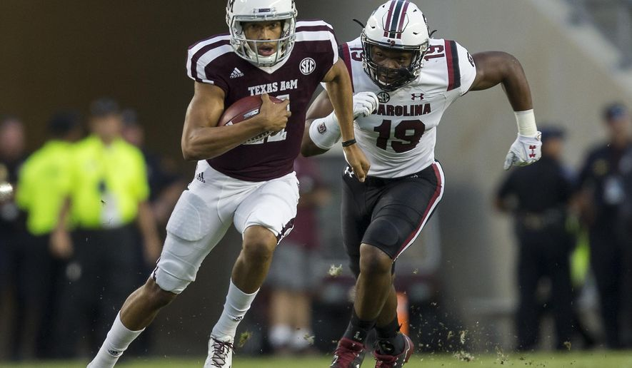 Texas A&M quarterback Kellen Mond (11) evades a tackle by South Carolina defensive lineman Brad Johnson (19) during the first quarter of an NCAA college football game Saturday, Sept. 30, 2017, in College Station, Texas. (AP Photo/Sam Craft)