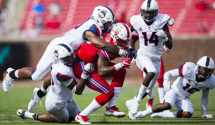 SMU wide receiver Courtland Sutton (16) is tackled by Connecticut defensive back Marshe Terry (41) and Connecticut defensive back Brice McAllister (16) during the second quarter of an NCAA college football game Saturday, Sept. 30, 2017, in Dallas. (Ashley Landis/The Dallas Morning News via AP)