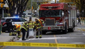 Crews clean up the scene where a van ran into pedestrians and later flipped over Saturday while being pursued by police, in Edmonton Alta, on Sunday, Oct. 1, 2017. The car and knife attack on a police officer outside a football game and a high-speed chase of a moving van that left four people injured appear to be the work of a single suspected terrorist, Canadian authorities said Sunday.(Jason Franson/The Canadian Press via AP)
