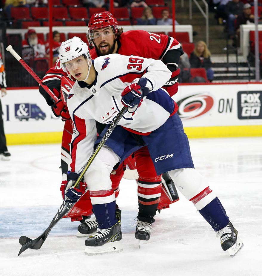 Washington Capitals' Alex Chiasson (39) battles Carolina Hurricanes' Justin Faulk (27) during the second period of an NHL hockey game, Friday, Sept. 29, 2017, in Raleigh, N.C. (AP Photo/Karl B DeBlaker)