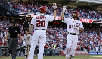 Washington Nationals' Anthony Rendon (6) celebrates with Daniel Murphy (20) after hitting a three-run home run during the first inning of a baseball game against the Pittsburgh Pirates, Sunday, Oct. 1, 2017, in Washington. (AP Photo/Mark Tenally)