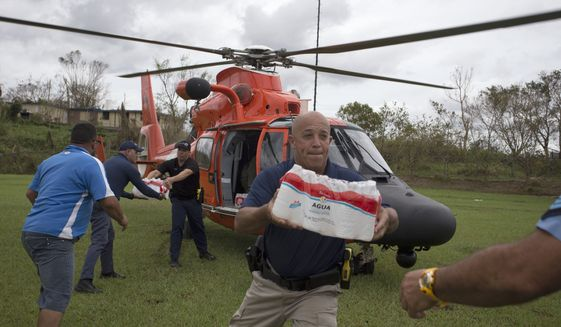 "A cost guard helicopter arrives to deliver emergency supplies after the passing of of Hurricane Maria, in Utuado, Puerto Rico, Saturday, Sept. 30 2017. San Juan Mayor Carmen Yulin Cruz on Friday accused the Trump administration of ""killing us with the inefficiency"" after the storm. She begged the president, who is set to visit Puerto Rico on Tuesday, to ""make sure somebody is in charge that is up to the task of saving lives,"" and appealed for help ""to save us from dying."" (Thais Llorca/Pool Photo via AP)"