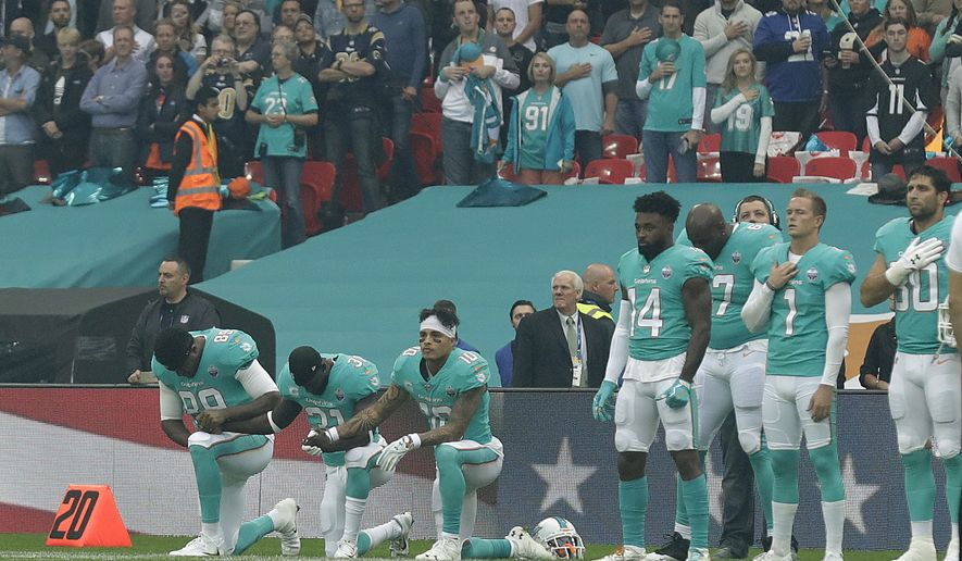 Miami Dolphins' Julius Thomas (89), Michael Thomas (31) and Kenny Stills take a knee as the U.S. national anthem is played before an NFL football game against the New Orleans Saints at Wembley Stadium in London, Sunday Oct. 1, 2017. (AP Photo/Matt Dunham)