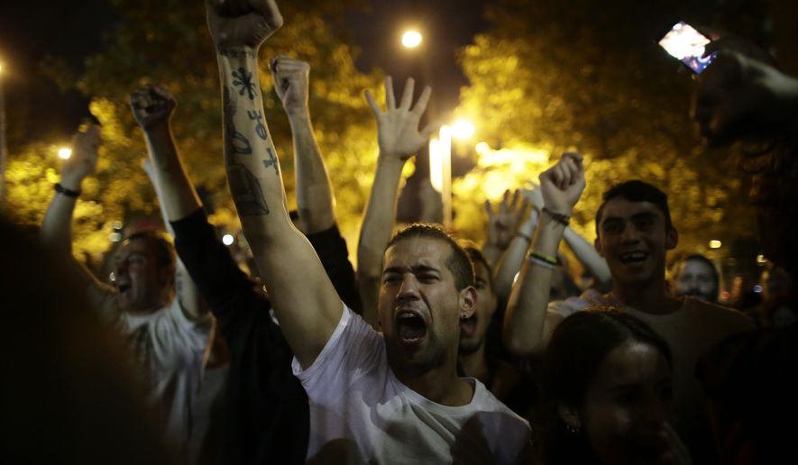Pro-referendum supporters celebrate on the street after the closing of a polling station assigned by the Catalan government in Barcelona, Spain, Sunday evening, 1 Oct. 2017. During the day Spanish riot police smashed their way into polling stations to try to halt a disputed independence referendum and fired rubber bullets at protesters. (AP Photo/Manu Fernandez)