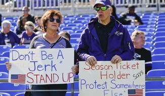 Gail Heiss and Micheal Goldberg hold up signs urging players to stand up during the playing of the National Anthem before an NFL football game between the Baltimore Ravens and the Pittsburgh Steelers in Baltimore, Sunday, Oct. 1, 2017. (AP Photo/Alex Brandon)