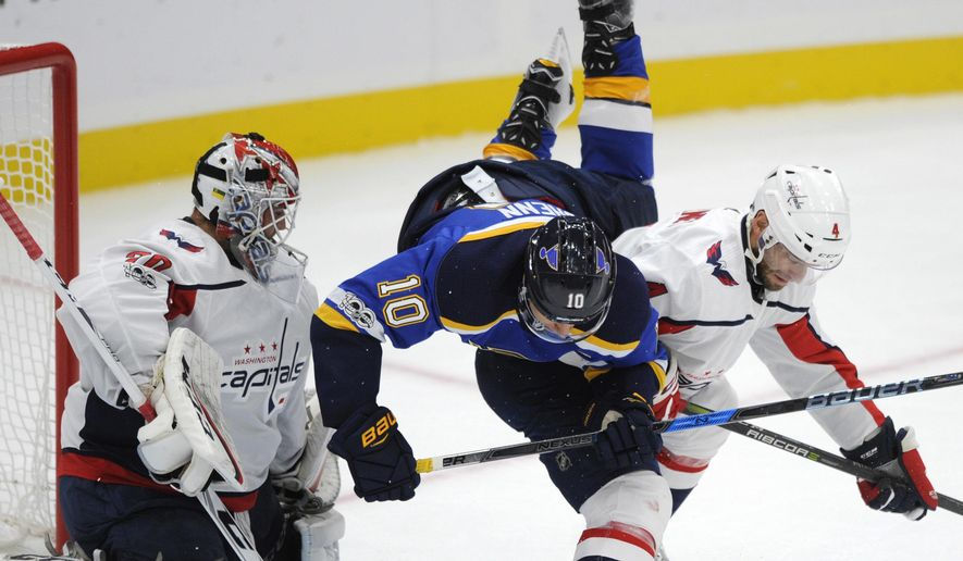 Washington Capitals' Taylor Chorney (4) checks St. Louis Blues' Brayden Schenn (10) as Capitals' Braden Holtby (70) looks on during the first period of a preseason NHL hockey game, Sunday, Oct. 1, 2017, in St. Louis. (AP Photo/Bill Boyce)