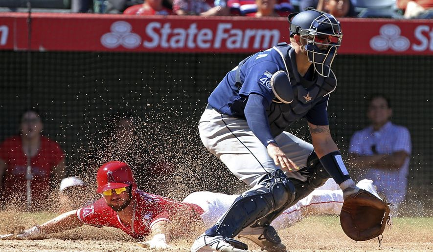 Seattle Mariners catcher Mike Marjama, right, waits for the throw from right field as Los Angeles Angels' Shane Robinson, left, scores on a Juan Graterol sacrifice fly in the seventh inning of a baseball game in Anaheim, Calif., Sunday, Oct. 1, 2017. (AP Photo/Reed Saxon)