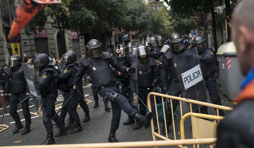 Spanish riot police removes fences thrown by people to them as they try to prevent people from reaching a voting site at a school assigned to be a polling station by the Catalan government in Barcelona, Spain, Sunday, 1 Oct. 2017. Catalan pro-referendum supporters vowed Saturday to ignore a police ultimatum to leave the schools they are occupying to use in a vote seeking independence from Spain. (AP Photo/Felipe Dana)
