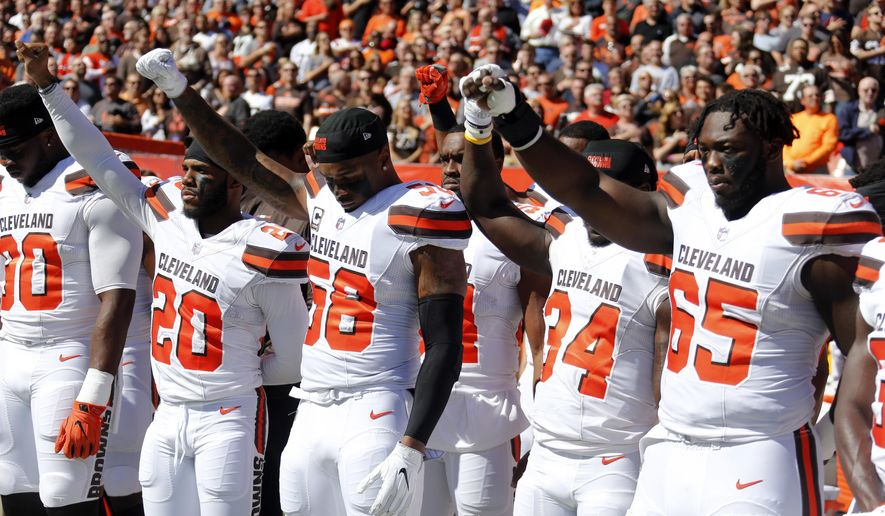 Cleveland Browns teammates raise their fists during the national anthem before an NFL football game against the Cincinnati Bengals, Sunday, Oct. 1, 2017, in Cleveland. (AP Photo/Ron Schwane)