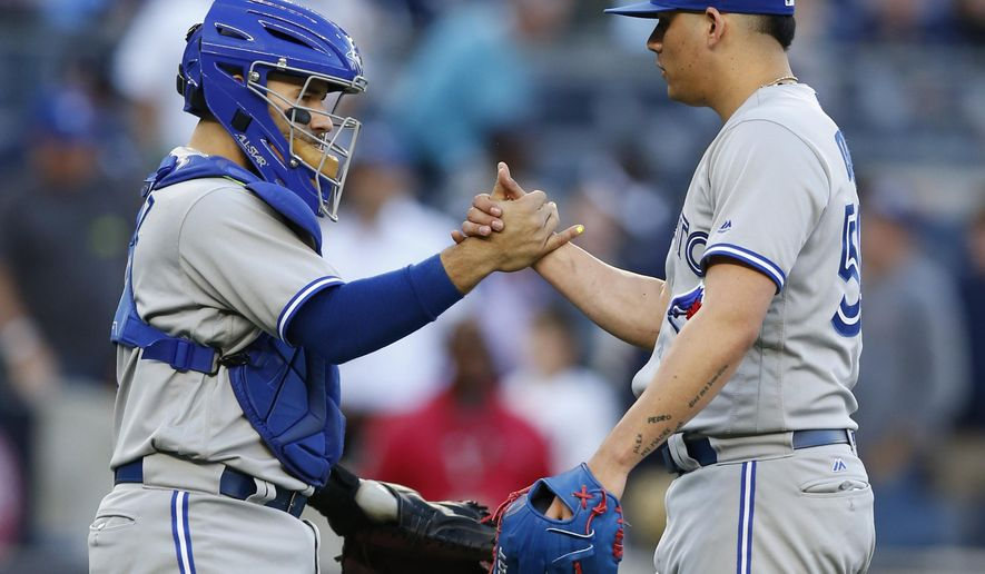 Toronto Blue Jays catcher Raffy Lopez (1) congratulates Blue Jays relief pitcher Roberto Osuna after the Blue Jays final regular season baseball game against the New York Yankees in New York, Sunday, Oct. 1, 2017. The Blue Jays defeated the Yankees 2-1. (AP Photo/Kathy Willens)