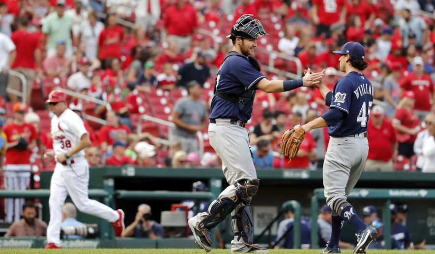 Milwaukee Brewers catcher Jett Bandy and pitcher Taylor Williams, right, shake hands as St. Louis Cardinals third base coach Mike Shildt, left, jogs off the field following a baseball game Sunday, Oct. 1, 2017, in St. Louis. The Brewers won 6-1. (AP Photo/Jeff Roberson)