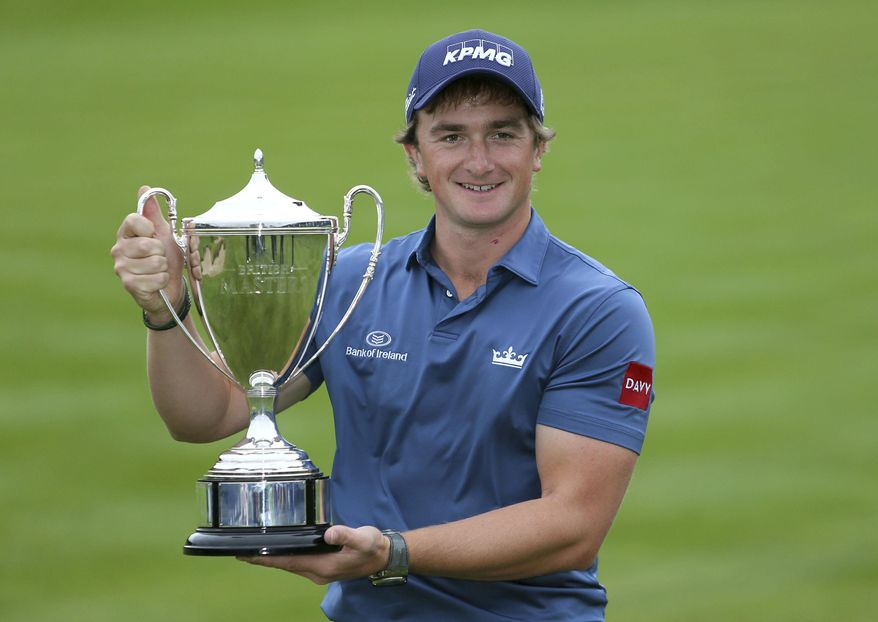 Ireland's Paul Dunne celebrates with the trophy during day four of the British Masters at Close House Golf Club, Newcastle, England, Sunday, Oct. 1, 2017. (Richard Sellers/PA via AP)
