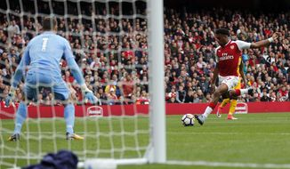 Arsenal's Alex Iwobi takes a shot to score his side's second goal during the English Premier League soccer match between Arsenal and Brighton and Hove Albion at the Emirates Stadium in London, Sunday, Oct. 1, 2017.(AP Photo/Frank Augstein)
