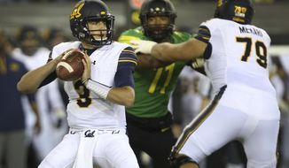 California quarterback Ross Bowers, left, looks down field under pressure from Oregon's Justin Hollins as he battles California's Patrick Mekari, right, during the first quarter of an NCAA college football game Saturday, Sept. 230, 2017, in Eugene, Ore. (AP Photo/Chris Pietsch)