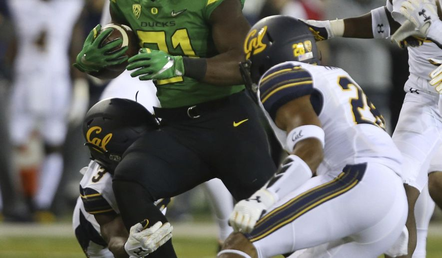 Oregon's Royce Freeman, center, rushes against California's Elijah Hicks, left, and Quentin Tartabull, right, during the first quarter of an NCAA college football game Saturday, Sept. 230, 2017, in Eugene, Ore. (AP Photo/Chris Pietsch)