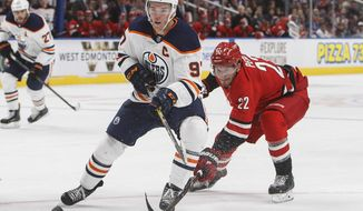FILE - In this Monday, Sept. 25, 2017 file photo, Carolina Hurricanes' Brett Pesce (22) chases Edmonton Oilers' Connor McDavid (97) during second period NHL preseason hockey action in Edmonton, Alberta.  Connor McDavid and Auston Matthews are at the forefront of a revival north of the 48th parallel as it seems like forever ago when no Canadian teams made the Stanley Cup Playoffs in 2015-16. (Jason Franson/The Canadian Press via AP, File)