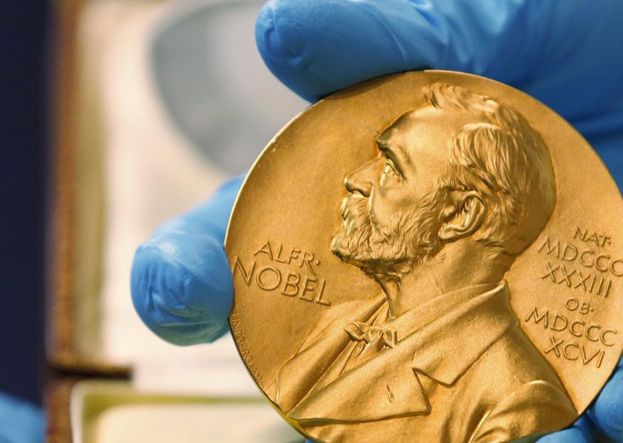 FILE- In this file photo dated Friday, April 17, 2015, a national library employee shows the gold Nobel Prize medal awarded to the late novelist Gabriel Garcia Marquez, in Bogota, Colombia. The Nobel prize has greater personal impact than merely receiving the monetary award, as it marks the recipient in terms of esteem and global recognition. (AP Photo/Fernando Vergara, FILE)