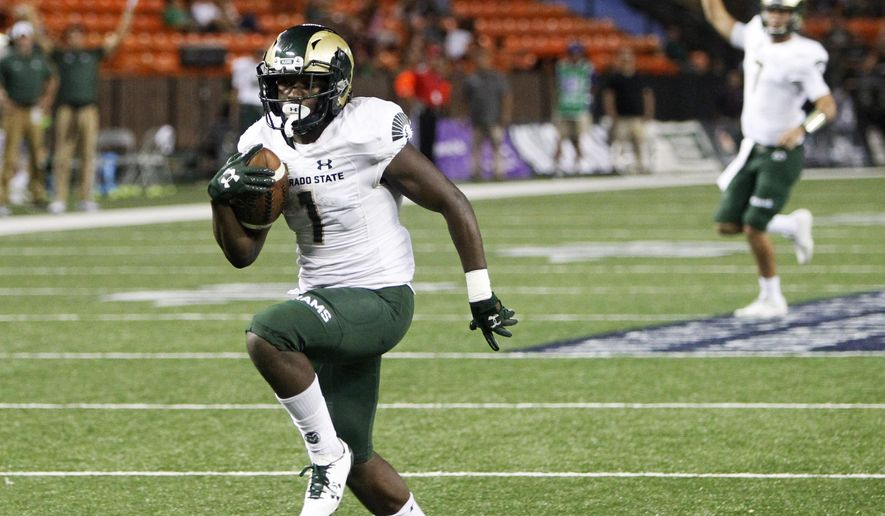 As Colorado State quarterback Nick Stevens (7) reacts in the background, wide receiver Michael Gallup (4) runs the ball in for a third quarter touchdown against Hawaii at the NCAA college football game, Saturday, Sept. 30, 2017, in Honolulu. (AP Photo/Marco Garcia)