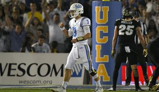 UCLA quarterback Josh Rosen, left, celebrates a touchdown as Colorado defensive back Ryan Moeller stands at right during the first half of an NCAA college football game, Saturday, Sept. 30, 2017, in Pasadena, Calif. (AP Photo/Mark J. Terrill)