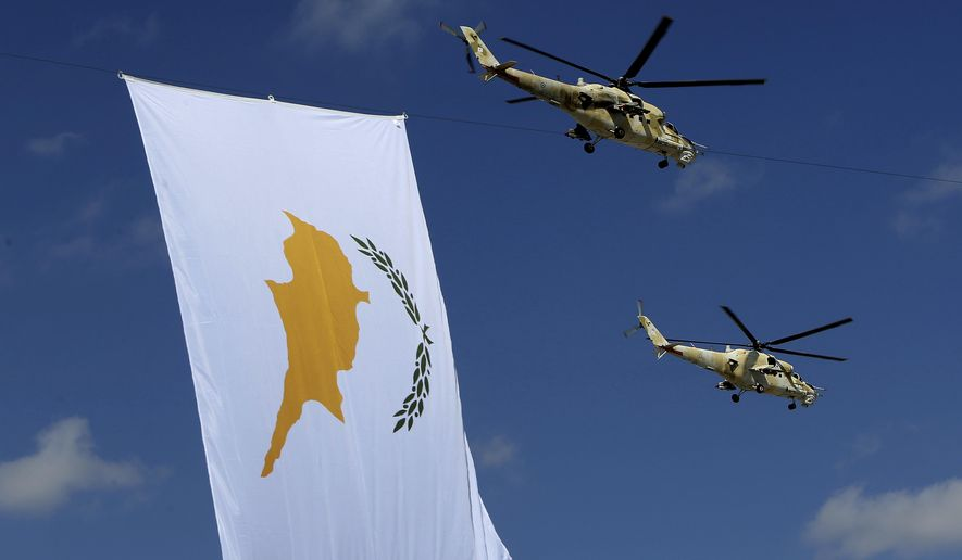 Russian-made military helicopters of the Cypriot air forces fly by a Cyprus' flag during a military parade marking the 57 years celebrations of independence, in Nicosia, in the divided island of Cyprus, Sunday, Oct. 1, 2017. The island of Cyprus has been divided since 1974, when Turkey invaded in response to a coup aimed at uniting the island with Greece. Cyprus gained independence from Britain in 1960.(AP Photo/Petros Karadjias)