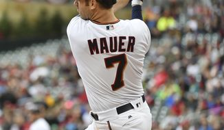 Minnesota Twins hitter Joe Mauer hits an RBI-double against the Detroit Tigers in the first inning of a baseball game, Sunday Oct. 1, 2017, in Minneapolis. (AP Photo/John Autey)